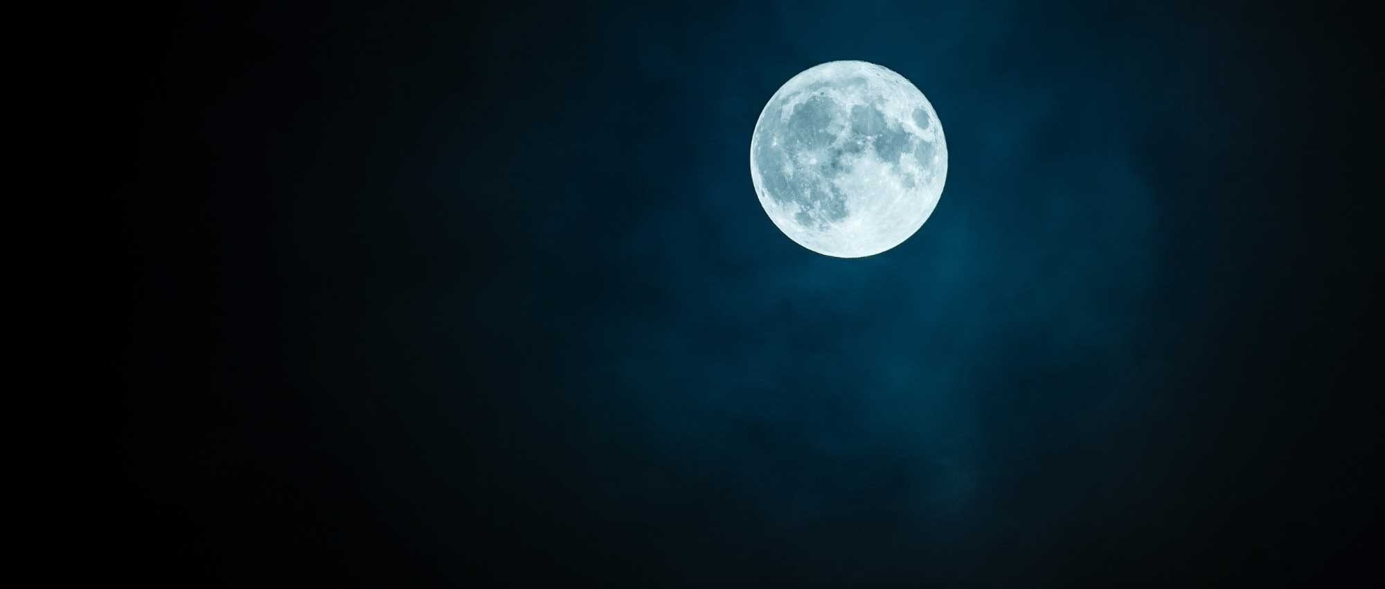 A bright full moon in an inky blue sky